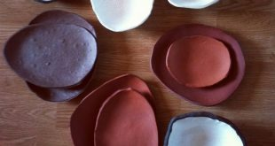 Plates and bowls formed over river rock in white black red clays. Linda Cato Pl ...
