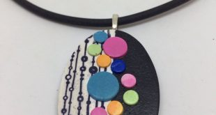 Polka dots on a Polymer clay pendant in black and primary colors in a geometric design